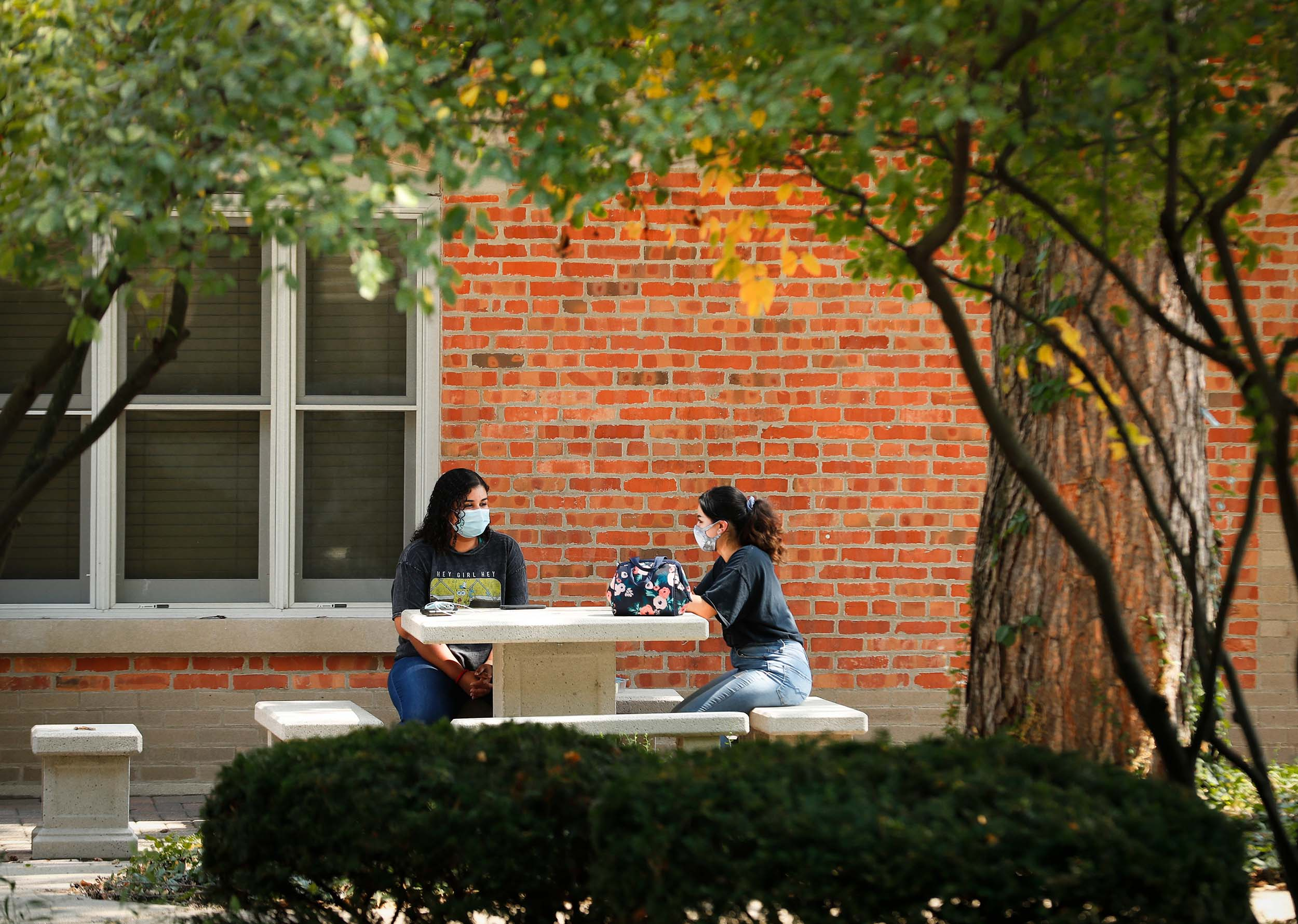 two female students sitting at table outside